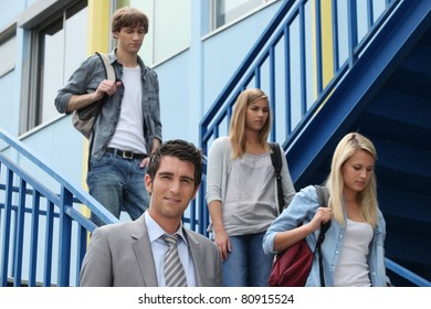 Three students walking down stairs alongside teacher