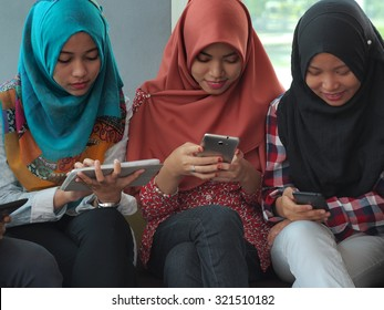 Three students wearing hijabs with mobile devices.
