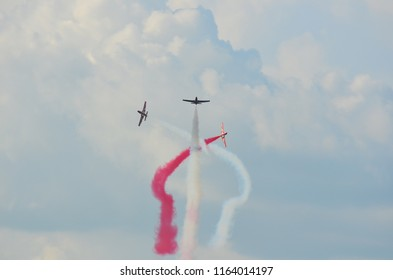 Three stunt jets perfoming a formation break and leaving red and white smoke trails on cloudy sky