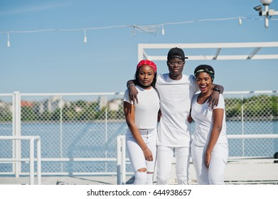 Three stylish african american friends, wear on white clothes at pier on beach. Street fashion of young black people. Black man with two african girls.