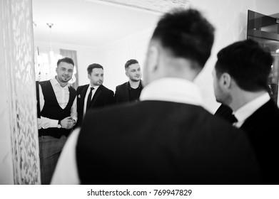 Three stylish bearded man well dressed, looking on mirror. Musician band guys.