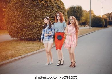 three stylish girls walking city and playground