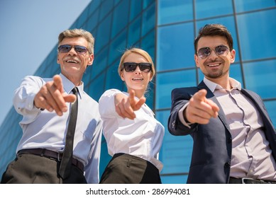 Three successful business people in suits posing to camera outdoors. Office background.
