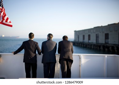 Three suited businessmen looking out across a harbor from the deck of a ship.