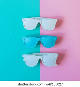 three sunglasses painted in white and blue on colorful background. summer fashion. minimal. flat lay