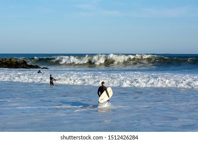 Three Surfers Going Out to the Lineup on a Swell from Hurricane Humberto at Rockaway Beach 67th Street, Queens, NY, USA on September 20th, 2019