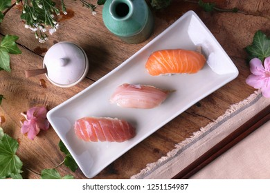 Three sushi on white plate table view.