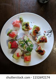 three sushi rolls on a plate. California roll, Caterpillar roll and Rainbow roll with wasabi and ginger.