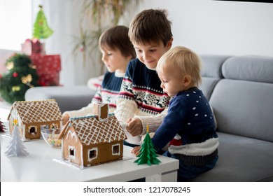 Three sweet boys, brothers, making gingerbread cookies house, decorating at home in front of the Christmas tree, child playing and enjoying, Christmas concept