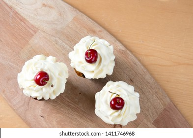 Three sweet cupcakes with creme and cherry top view
