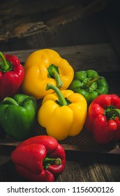 Three sweet peppers on a wooden table background.
