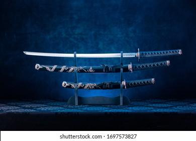 Drei Schwerter auf Stehen, Katana Blade ausgesetzt, blaues Licht hinter