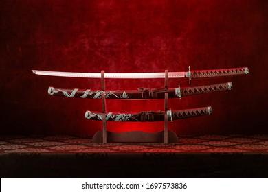 Three swords on stand, katana blade exposed, red light behind