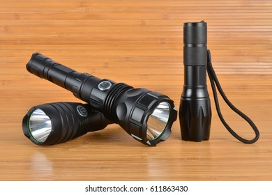 Three tactical flashlights on a wood background