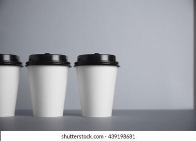 Three take away white paper cups with black caps on left side of image, isolated on simple gray background