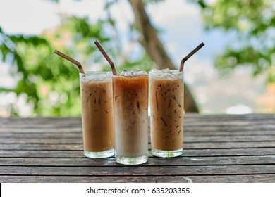 Three tall glasses of iced coffee on old wooden table.