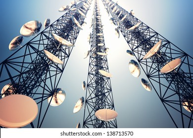 Three tall telecommunication towers with antennas on blue sky. View from the bottom.
