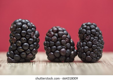 Three tasty blackberry fruit on a red background. Front view