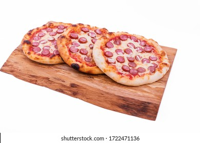 Three tasty pepperoni pizzas. Top view of hot pepperoni pizzas on a wooden tray, board, dish. The object is isolated on a white background.