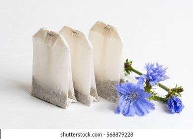 three tea bags with chicory on white