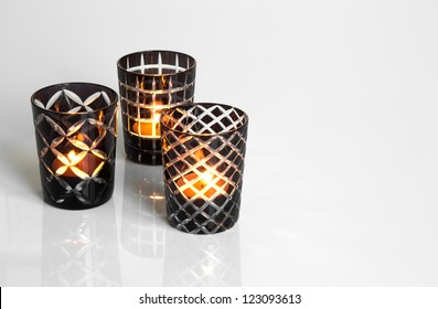 Three tealights in black and white candleholders, on reflective surface.
