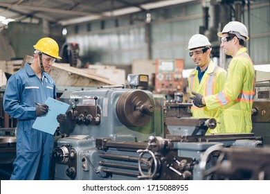 Three technician inspecting complex metal component at machine in factory