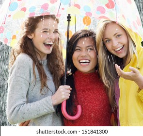 Three Teenage Girl Sheltering From Rain Beneath Umbrella
