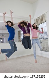 Three teenage girlfriends leaping and dancing to music at home in a carpeted living room