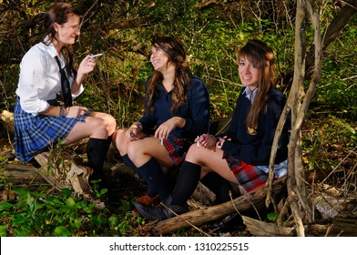 Three teenage girls after school hiding in a forest to smoke cigarettes
