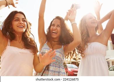 Three Teenage Girls Dancing Outdoors Against Sun