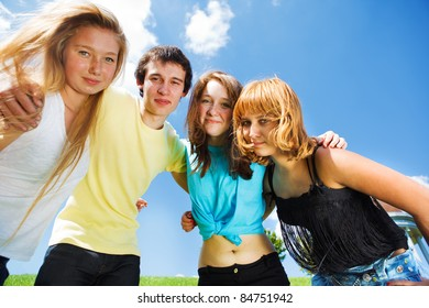 Three teenage girls and a guy embracing