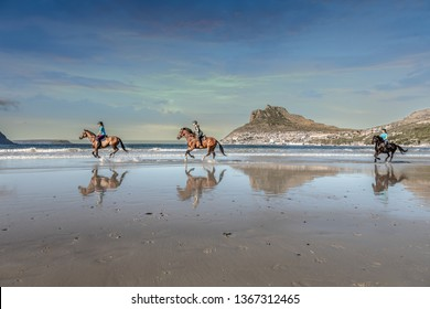 Three teenage girls on horseback cantering in the water at low tide on the beach under a cloud sky with a beautiful mountain in the background and reflections of themselves in the water on the shore