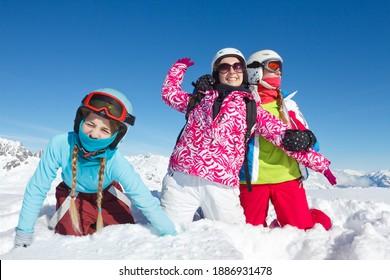 Trois adolescentes en vacances d'hiver dans les montagnes, assises dans la neige fraîche, regardent la caméra. Paysage avec grand ciel bleu et vêtements colorés
