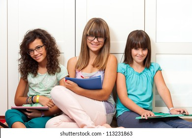 Three teenage girls sitting with files and notebooks indoors.