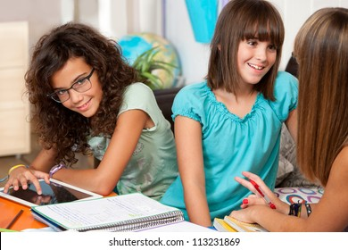 Three teenage students discussing their homework at desk.