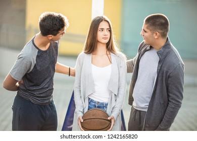Three teenagers playing basketball