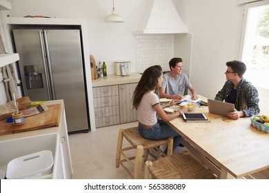 Three teens study in kitchen using computers, elevated view