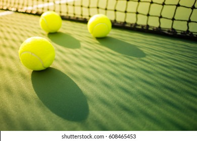 three tennis balls on green hard court with shadow from net