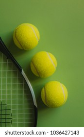 Three tennis balls and a racket on green background.