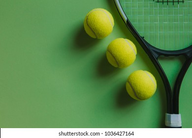 Three tennis balls and a racket on green background, with copy space on the left.