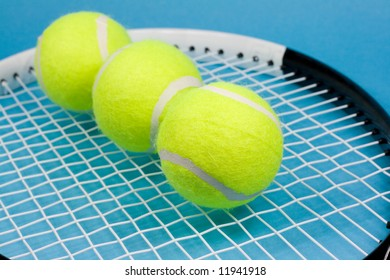 Three tennis balls and racket on blue background