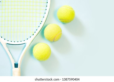 Three tennis balls and white racquet on blue background. Trendy minimal design top view pastel colours