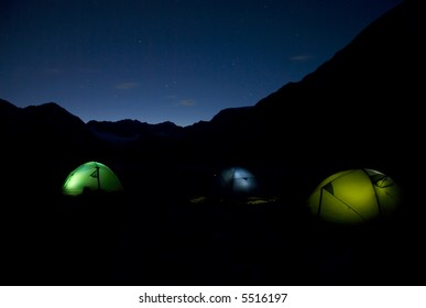 Three tents illuminated from inside at night in the mountain range