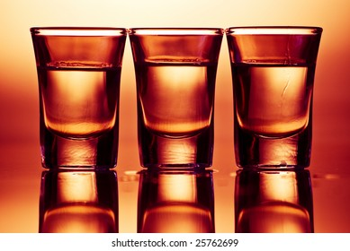 three tequila drinks in red light