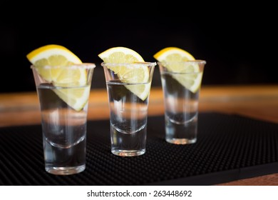 Three tequila shots with lemon on a bar ribber mat. Shallow DOF and toned