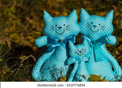 Three textile toys of a cat, sitting together on a yellow foliage, in a meadow. Family concept, child protection. Rummy background. There is a place for text.