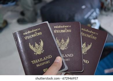 Three Thai passports in hand, travel concept