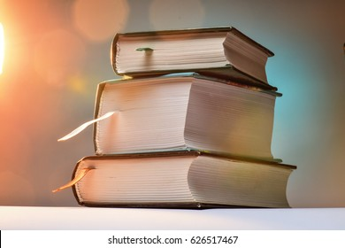Three thick books on an abstract background with blurred lights.
