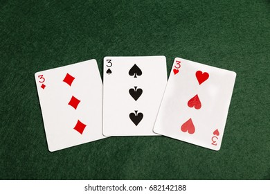 Three threes laid out on a green baize background.