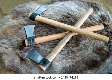 Three throwing tomahawks displayed on a beaver fur with bokeh effect. These hawks are made from a horseshoe rasp.